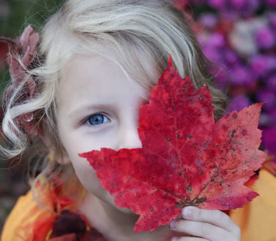girl holding leaf to her face
