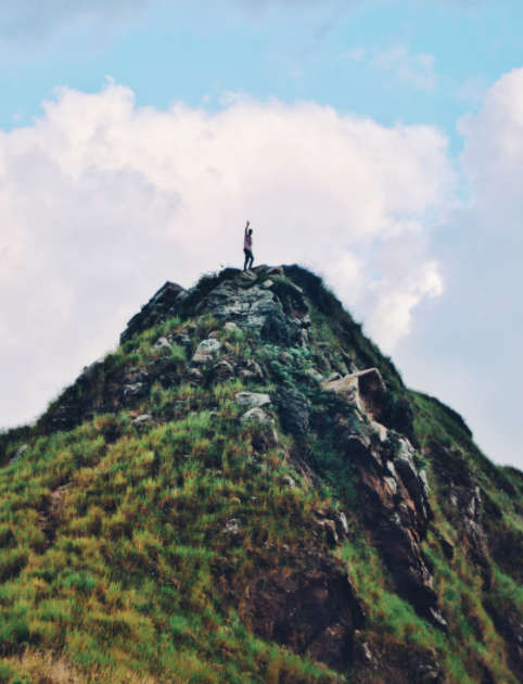 man on top of mountain with fist raised